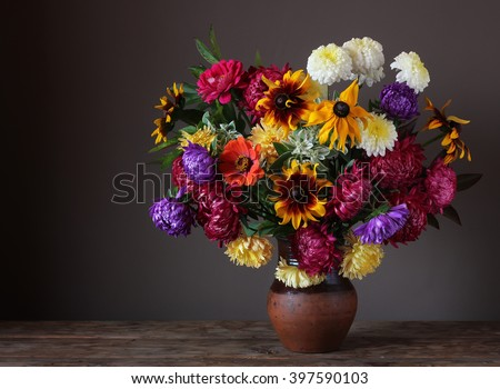 Still life with chrysanthemums and asters in a clay jug in rustic style on a dark background. Place for text on the left. - stock photo