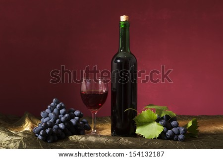 Still life with clusters of dark grapes and wine - stock photo