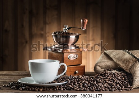 still life with coffee beans and old coffee mill on the wooden background  - stock photo