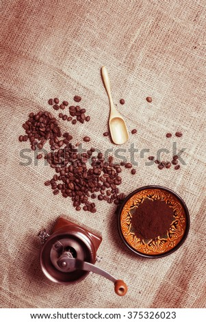 Still life with coffee beans, coffee mill, cup and a wooden spoon on the background of sackcloth. Top view. Toned image. - stock photo