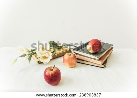Still life with concept of education apple red three results sitting on a pile of school books the background is white. - stock photo