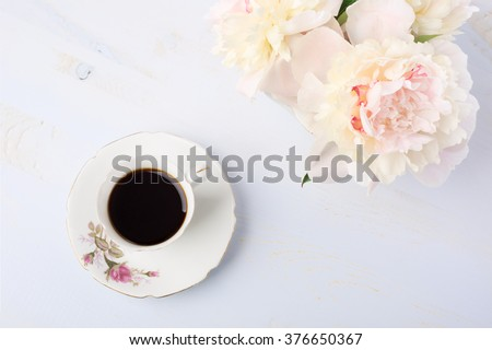 Still life with cup of coffee and flowers (peonies) on light  lilac wooden table. - stock photo