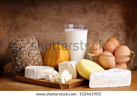 still life with dairy products, milk, eggs, bread and cheese on a vintage wooden background - stock photo