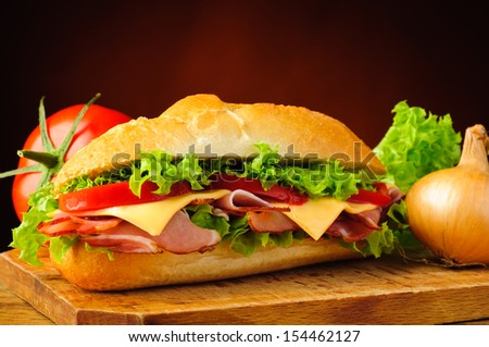 still life with delicious deli sub sandwich and vegetables - stock photo