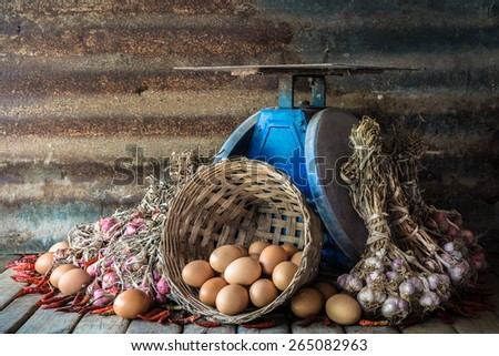 Still life with eggs, onions, garlics, pepper and old blue scales on wood table with grunge steel plate background - stock photo