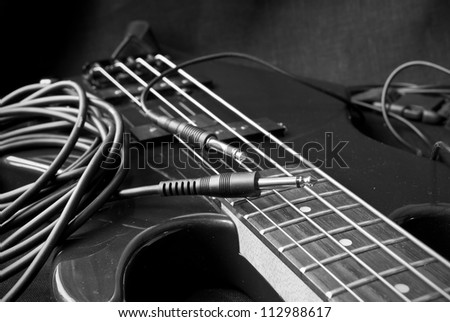 still life with electrical guitar and jacks; black and white - stock photo