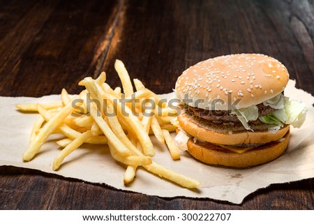 still life with fast food hamburger menu, french fries on wood desk - stock photo