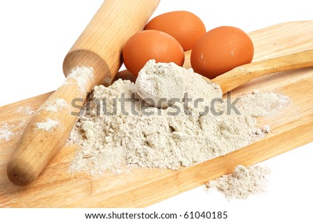 Still life with flour and eggs on a wooden board - stock photo