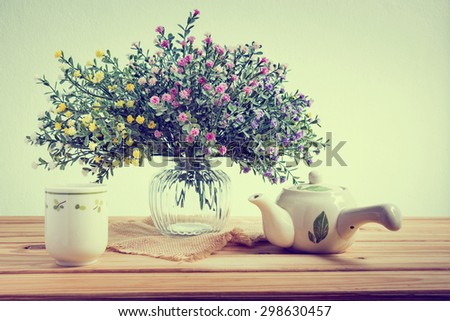 Still life with flowers and cup of tea on wooden table over grunge background - stock photo