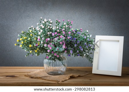 Still life with flowers and white vintage photo frame on wooden table over grunge background - stock photo