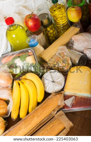 Still life with food purchases from supermarket  on table in home - stock photo