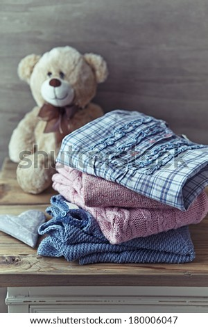 Still Life with Girls Sweaters on a Chest of Drawers - stock photo