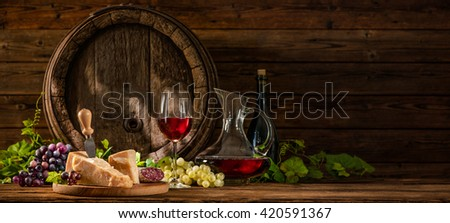 Still life with glass of red wine and old oak wine barrel - stock photo