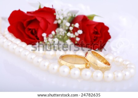 Still life with golden wedding rings and red roses - stock photo