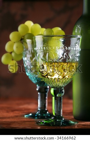 still life with golden wine in old-time goblet and grape - stock photo