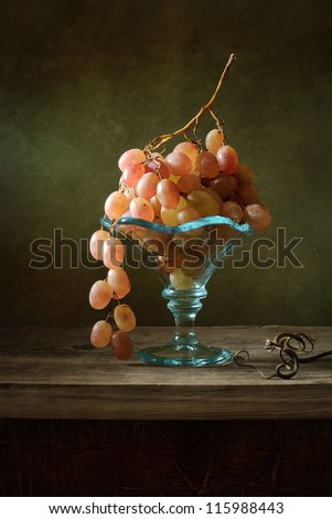 Still life with grapes in a blue bowl - stock photo
