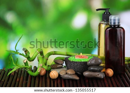 Still life with green bamboo plant and stones, on bamboo mat, on bright background - stock photo