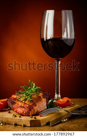 still life with grilled steak, rosemary and glass of red wine - stock photo