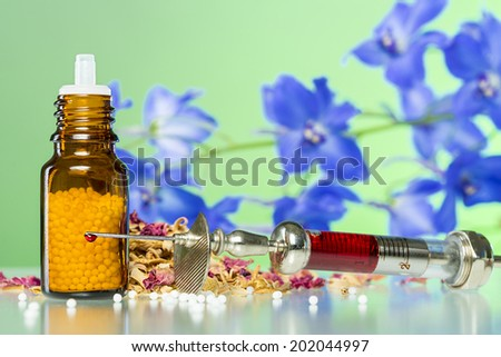 still life with homeopathy globule, syringe with blood, some spices and flowers. - stock photo