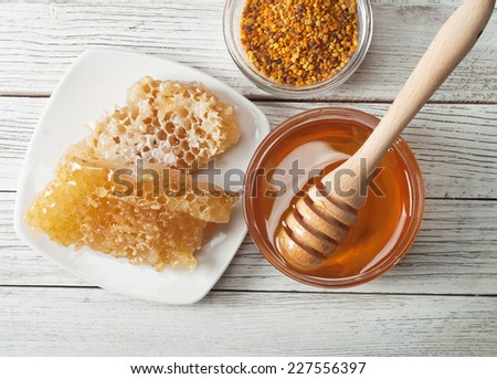 Still life with honey, honeycomb, pollen - stock photo