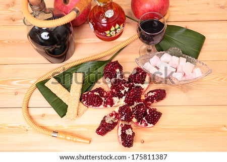 Still-life with Hookah, wine, garnet and sweets - stock photo