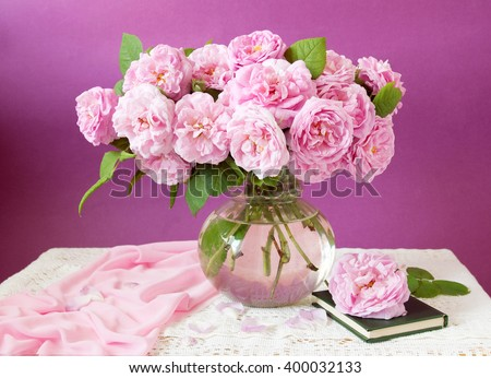 Still life with huge bunch of pink roses, books and globe on painting background - stock photo