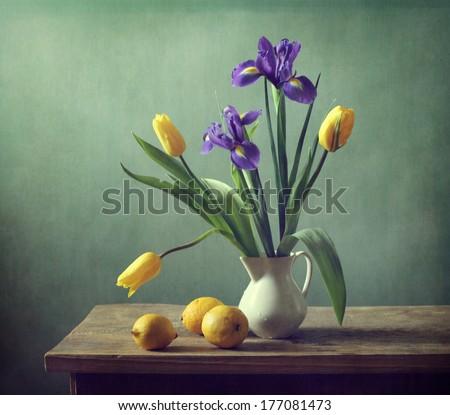 Still life with irises, lemons and tulips - stock photo