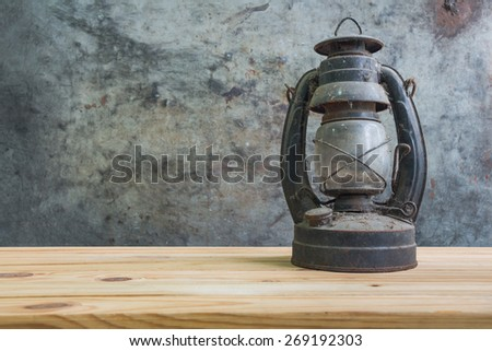 still life with kerosene lamp on wooden table over grunge background - stock photo