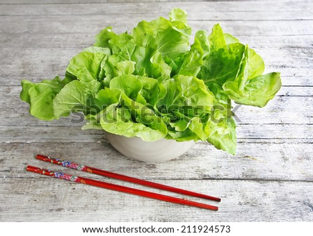 still life with lettuce in a bowl on wooden table  - stock photo