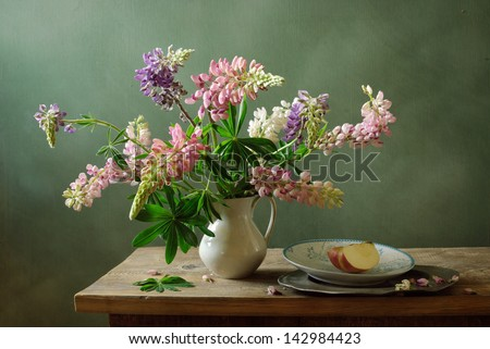 Still life with lupines and a sliced apple - stock photo