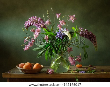 Still life with lupines and apricots - stock photo