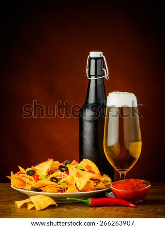 still life with nachos, salsa dip and glass and bottle of beer - stock photo