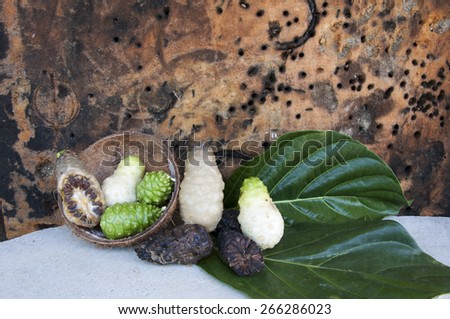 Still Life with Noni ,dry Noni and coconut shell on the Brown background - stock photo