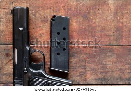 Still life with old black handgun near holder on nice wooden background - stock photo