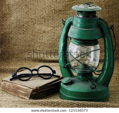 Still life with old book Kerosene lamp and glasses. - stock photo