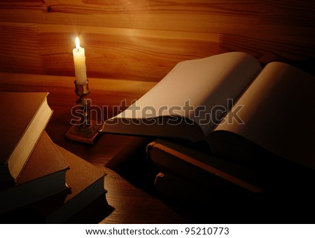 still life with old books and burning candle - stock photo