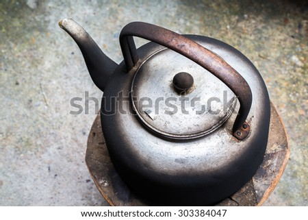 still life with old dirty Kettle on old stove - stock photo