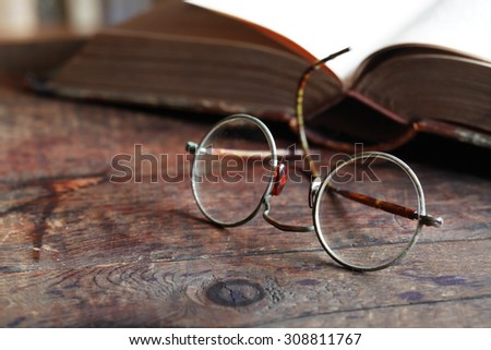Still life with old spectacles near open book on wooden table - stock photo