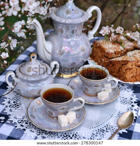 Still life with old tea set and home cake on white napkin, afternoon tea in the spring garden  - stock photo