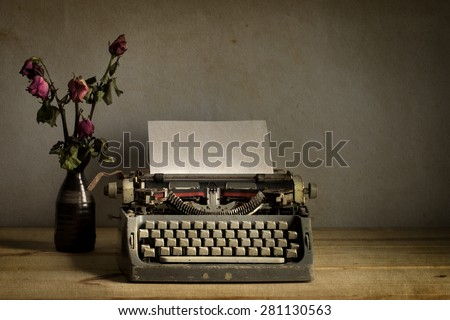 Still life with old typewriter with dry rose flowers on wooden  table - stock photo
