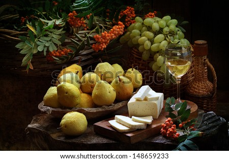 Still-life with pears and white wine, juicy ripe pears with sweet grapes salty cheese and white fragrant wine - stock photo