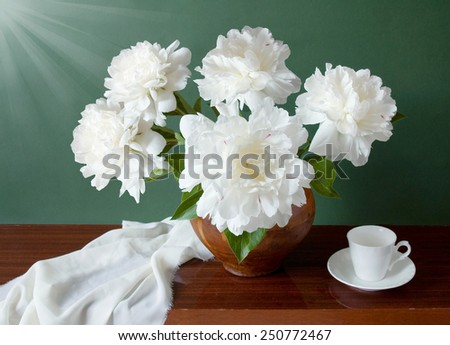 Still life with peony flowers and cup on artistic background - stock photo