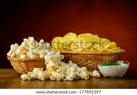 still life with potato chips, popcorn and dill dip sauce - stock photo