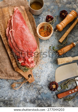 Still life with raw fillet steaks over on vintage cutting board with kitchen tools and seasoning. Rustic tools.  - stock photo