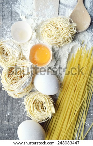 still life with raw homemade pasta and ingredients for pasta.till life with raw homemade pasta and ingredients for pasta.process of cooking pasta - stock photo