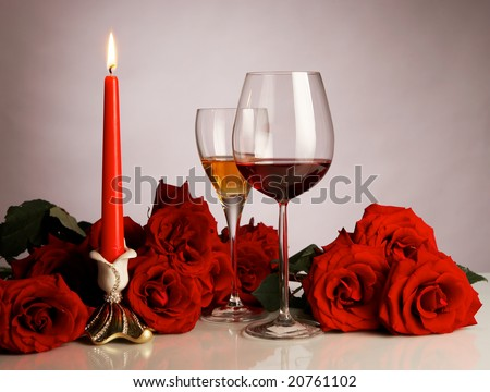 Still-life with red roses, glasses and a candle - stock photo