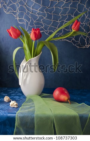 Still life with red tulips and red pear - stock photo