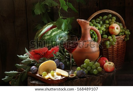 Still-life with red wine and fresh fruit, fragrant red wine in a graceful glass and cream cheese both juicy sweet apples and plum and both a striped water-melon and clusters of ripe green grapes - stock photo