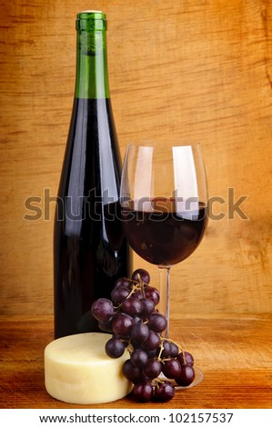 still life with red wine, cheese and grapes - stock photo