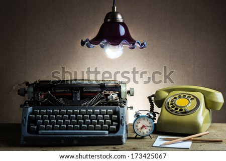 Still life with retro typewriter, alarm clock, telephone and old lantern - stock photo